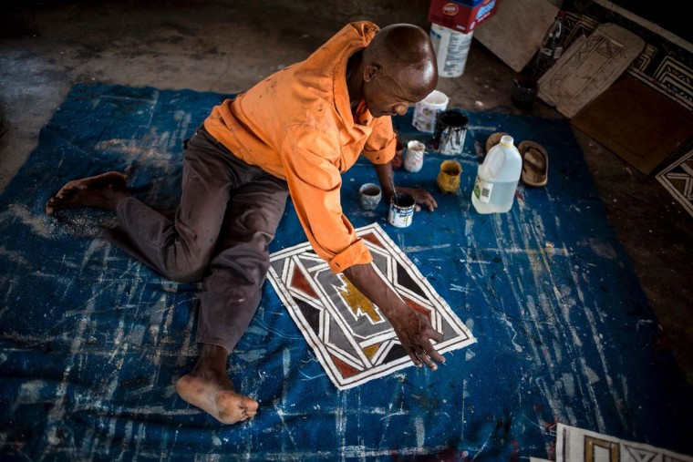 A student of South African artist Esther Mahlangu, 81, paints a design in her home in Mabhoko Village, Siyabuswa, Mpumalanga on March 6, 2017. Mahlangu recently opened her exhibition at the Melrose Gallery where her series of artwork inspired by Nelson Mandela was unveiled on March 1. The artist has produced six paintings reproduced from drawings created by Mandela in her signature Ndebele style. The exhibition will include previous work by Mahlangu. (GULSHAN KHAN/AFP/Getty Images)