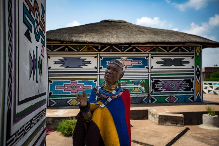 South African artist Esther Mahlangu, 81, gestures at her home in Mabhoko Village, Siyabuswa, Mpumalanga on March 6, 2017. Mahlangu recently opened her exhibition at the Melrose Gallery where her series of artwork inspired by Nelson Mandela was unveiled on March 1. The artist has produced six paintings reproduced from drawings created by Mandela in her signature Ndebele style. The exhibition will include previous work by Mahlangu. (GULSHAN KHAN/AFP/Getty Images)