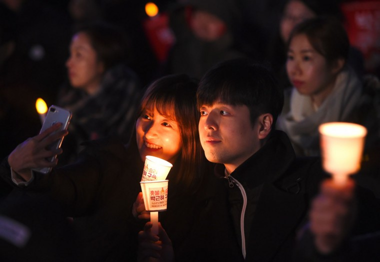 A couple take a selfie during a candlelit rally demanding arrest of the impeached-president in Seoul on March 10, 2017 after the announcement of the Constitutional Court's decision to uphold the impeachment of South Korea's President Park Geun-Hye. South Korean President Park Geun-Hye was fired on March 10 as a court upheld her impeachment over a corruption scandal that has paralysed the nation at a time of mounting tensions in East Asia. / (AFP Photo/Jung Yeon-je)