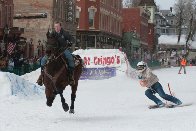 Rider Dana Stiles races down Harrison Avenue towing skier Mike Fries during the 68th annual Leadville Ski Joring weekend competition on March 5, 2017 in Leadville, Colorado. Skijoring, which has its origins as a competitive sport in Scandinavia, has been adapted over the years to include a team made up of a rider and skier who must navigate jumps, slalom gates, and the spearing of rings for points. Leadville, with an elevation of 10,152 feet (3,094 m), the highest incorporated city in North America, has been hosting skijoring competitions since 1949. (Jason Connolly/AFP/Getty Images)