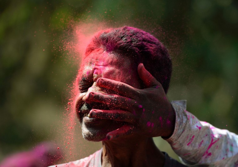 An Indian man is smeared with coloured powder during the Holi celebrations in Mumbai on March 13, 2017. Holi, the festival of colours, is a riotous celebration of the coming of spring and falls on the day after full moon annually in March. (Punit Paranjpe/AFP/Getty Images)