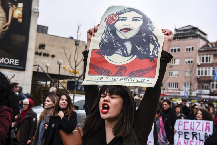 """A woman holds a poster by US artist Shepard Ferey and reading """"We the people, defend dignity"""" as Kosovo feminist supporters take part in a rally for gender equality and against violence towards women to mark the International Women's Day in Pristina on March 8, 2017. (ARMEND NIMANI/AFP/Getty Images)"""