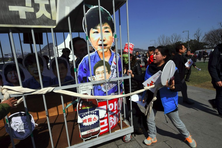 Anti-government activists carry a mock prison containing a board-cut of South Korea's President Park Geun-Hye after the announcement of the Constitutional Court's decision to uphold the impeachment of Park in Seoul on March 10, 2017.South Korean President Park Geun-Hye was fired by the country's top court on March 10, as it upheld her impeachment by parliament over a wide-ranging corruption scandal. / (AFP Photo/Jung Yeon-je)