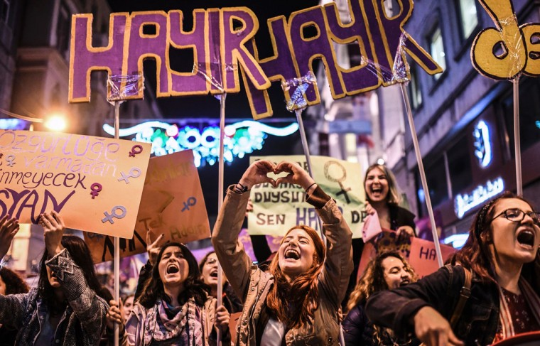 "A woman makes a heart sign with her hands as people hold signs reading ""no"" as they march down Istiklal Avenue during a feminist night march to mark International Women's Day in Istanbul on March 8, 2017. (BULENT KILIC/AFP/Getty Images)"