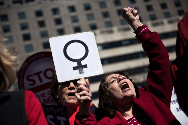 Activists protest the Trump administration and rally for women's rights during a march to honor International Woman's Day on March 8, 2017 in Washington, DC. (BRENDAN SMIALOWSKI/AFP/Getty Images)