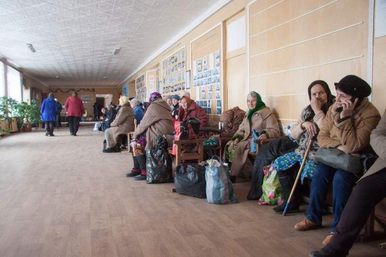 """People, who were evacuated due to a fire raging at a military munitions depot near the city of Balakliya, wait on March 23, 2017 at a school in the village of Savintsy in the Kharkiv province of eastern Ukraine. Ukraine said that a fire raging at a munitions depot (caused by a series of explosions) in the country's east, which the military blamed on an """"act of sabotage"""", could continue for up to a week. """"We can evaluate everything as the intensity of the fire decreases,"""" Ukrainian Prime Minister said in televised comments. / (AFP Photo/Sergey Bobok)"""