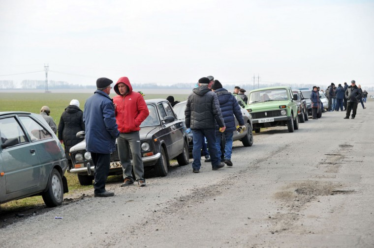 """People, who were evacuated due to a fire raging at a military munitions depot, wait next to their vehicles on March 23, 2017 near the city of Balakliya, in the Kharkiv province of eastern Ukraine. Ukraine said that a fire raging at a munitions depot (caused by a series of explosions) in the country's east, which the military blamed on an """"act of sabotage"""", could continue for up to a week. """"We can evaluate everything as the intensity of the fire decreases,"""" Ukrainian Prime Minister said in televised comments. / (AFP Photo/Sergey Bobok)"""