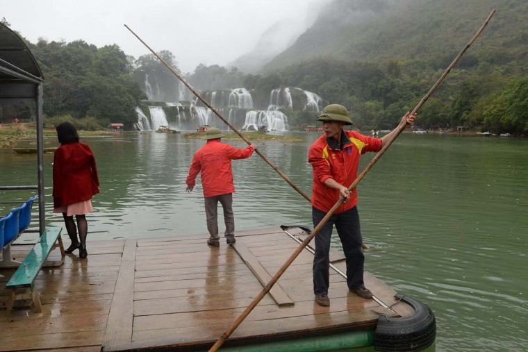This picture taken on March 12, 2017 shows Vietnamese tourist raft operators using bamboo rods to push their vessel along the waters in front of the Thac Ban Gioc or Ban Gioc falls, located on the Vietnam-China land border area in Trung Khanh district, Vietnam's northern province of Cao Bang. (HOANG DINH NAM/AFP/Getty Images)