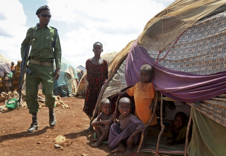 In this photo taken Saturday, March 25, 2017, a Somali policeman walks past as newly displaced Somali children stand outside their makeshift shelter at a camp in Baidoa, Somalia. Somalia's drought is threatening 3 million lives according to the U.N. and in recent months aid agencies have been scaling up their efforts but say more support is urgently needed to prevent the crisis from worsening. (AP Photo/Farah Abdi Warsameh)