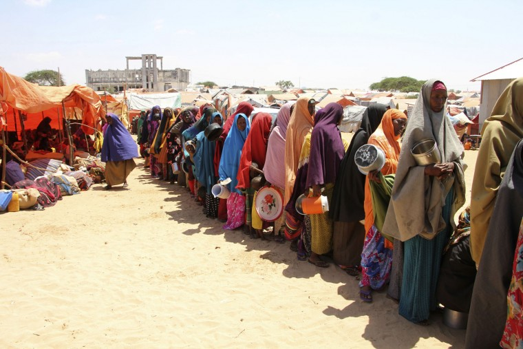 Displaced Somali women stand in a queue to receive food handouts in a camp, just outside of Mogadishu, in Somalia, Monday, March, 27, 2017. Somalia's drought is threatening 3 million lives, according to the U.N. In recent months, aid agencies have been scaling up their efforts but they say said more support is urgently needed to prevent the crisis from worsening. (AP Photo/Farah Abdi Warsameh)