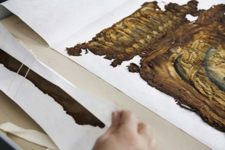 "A conservator reveals some pieces of a Barberini tapestry that were damaged in a 2001 fire at the Textile Conservation Laboratory at the Cathedral of St. John the Divine in New York, Wednesday, March 22, 2017. Experts at the cathedral just spent 16 years sprucing up its super-size wall hangings with a labor-intensive process that uses dental probes, tweezers and other tools. Now the historic house of worship is inviting the public to enjoy the fruits of its labors. An exhibit called ""The Barberini Tapestries, Scenes from the Life of Christ"" runs through June 25. (AP Photo/Seth Wenig)"