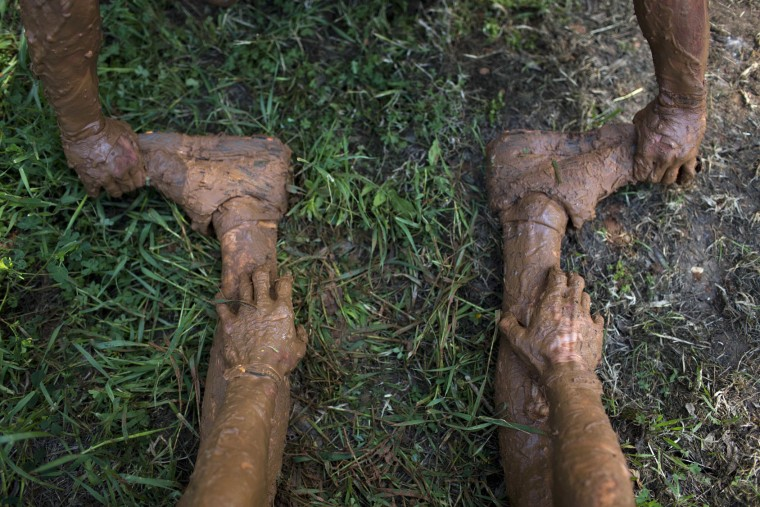 A participant suffers from a muscle cramp in his leg during the Mud Day race, a 13 kilometer obstacle course in Tel Aviv, Israel, Friday, March 24, 2017. (AP Photo/Oded Balilty)