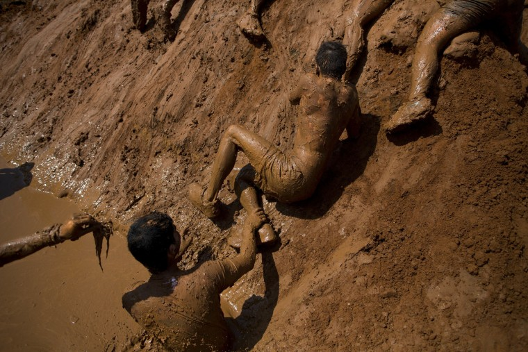 People take part in the Mud Day race, a 13 kilometers obstacle course in Tel Aviv, Israel, Friday, March 24, 2017. (AP Photo/Oded Balilty)