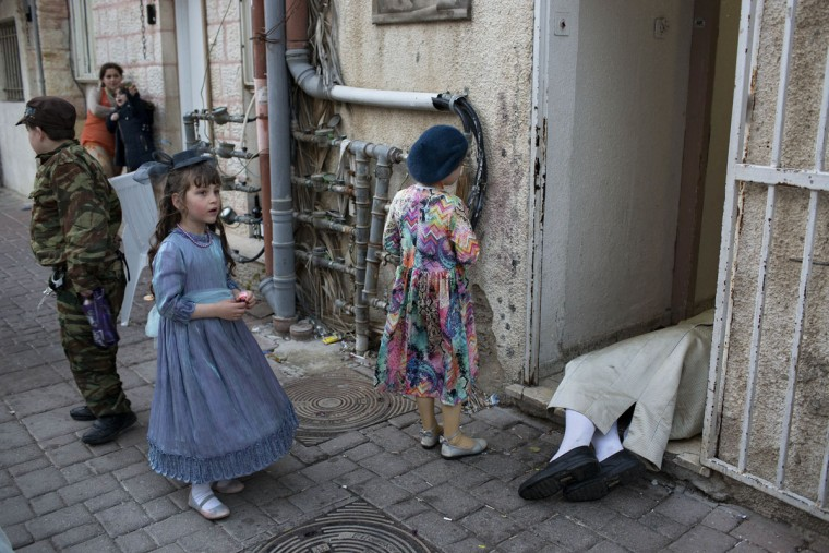 Ultra-Orthodox Jewish kids in costumes looking at a passed out drunk man during the Jewish holiday of Purim in Mea Shearim ultra-Orthodox neighborhood in Jerusalem, Monday, March 13, 2017. The Jewish holiday of Purim celebrates the Jews' salvation from genocide in ancient Persia, as recounted in the Scroll of Esther. (AP Photo/Oded Balilty)