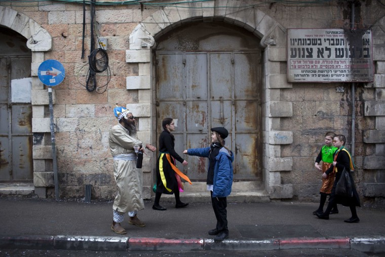 An Ultra-Orthodox Jewish man and kids wear costumes during the Jewish holiday of Purim in Mea Shearim ultra-Orthodox neighborhood in Jerusalem, Monday, March 13, 2017. The Jewish holiday of Purim celebrates the Jews' salvation from genocide in ancient Persia, as recounted in the Scroll of Esther. (AP Photo/Oded Balilty)