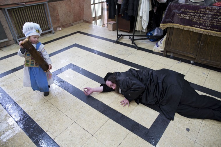 An Ultra-Orthodox Jewish man lies on the ground after getting drunk during the Jewish holiday of Purim in Mea Shearim ultra-Orthodox neighborhood in Jerusalem, Monday, March 13, 2017. The Jewish holiday of Purim celebrates the Jews' salvation from genocide in ancient Persia, as recounted in the Scroll of Esther. (AP Photo/Oded Balilty)