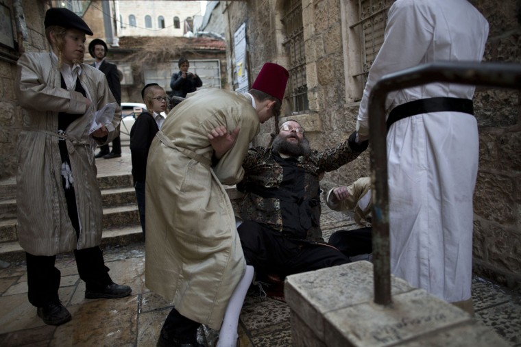 Ultra-Orthodox Jewish men help a drunk man as they celebrates the holiday of Purim in Mea Shearim ultra-Orthodox neighborhood in Jerusalem, Monday, March 13, 2017. The Jewish holiday of Purim celebrates the Jews' salvation from genocide in ancient Persia, as recounted in the Scroll of Esther. (AP Photo/Oded Balilty)