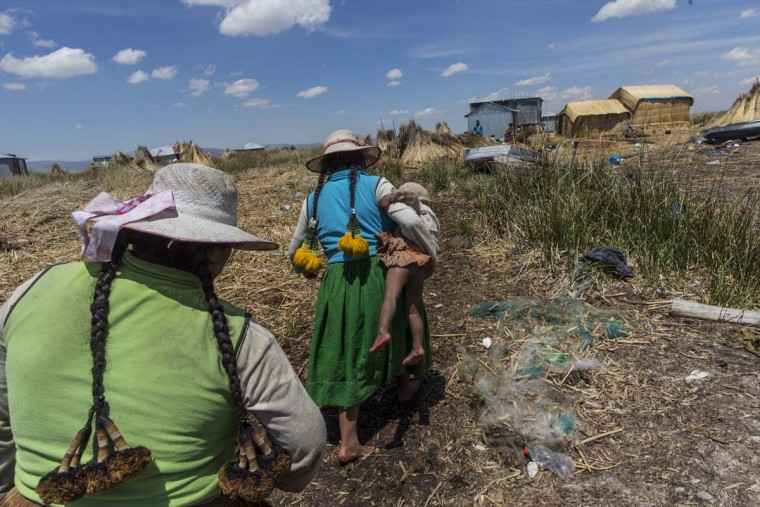 In this Feb. 2, 2017 photo, a woman carries her baby home in Kapi Cruz Grande, a village on the trash filled shores of Lake Titicaca in the Puno region of Peru. Peru's new president, Pedro Pablo Kuczynski, a former Wall Street banker who lived just 40 kilometers (25 miles) from the lake as a youth, has made access to clean water one of the priorities of his presidency. (AP Photo/Rodrigo Abd)