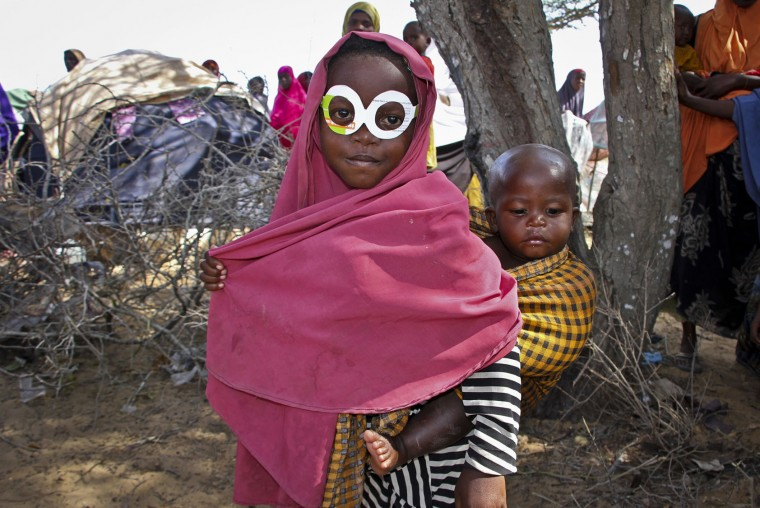 A young Somali girl who was displaced by the drought wears a pair of mock spectacles cut out from a cardboard box of antibiotics medicine as a joke, as she carries her brother around a camp just outside of Mogadishu, in Somalia Tuesday, March 28, 2017. Somalia's drought is threatening 3 million lives according to the U.N. and in recent months aid agencies have been scaling up their efforts but say more support is urgently needed to prevent the crisis from worsening. (AP Photo/Farah Abdi Warsameh)
