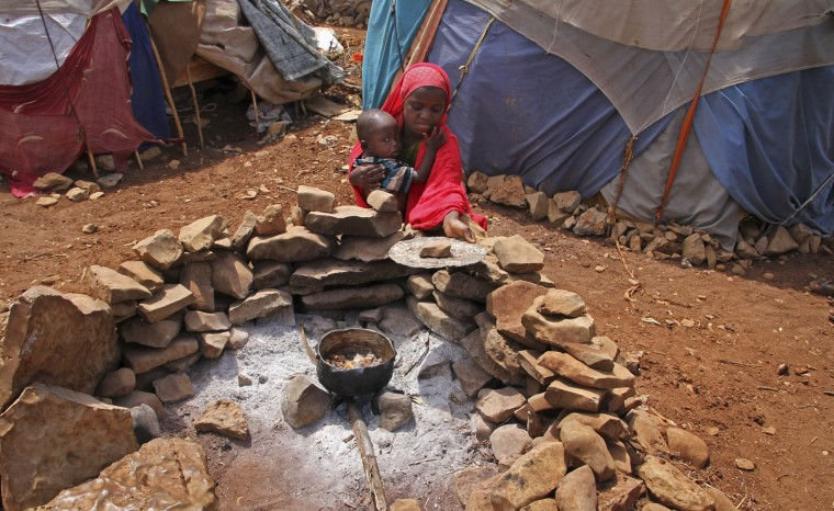 In this photo taken Saturday, March 25, 2017, a newly displaced Somali girl holds her sister as they cook food over a fire, next to their makeshift shelter at a camp in Baidoa, Somalia. Somalia's drought is threatening 3 million lives according to the U.N. and in recent months aid agencies have been scaling up their efforts but say more support is urgently needed to prevent the crisis from worsening. (AP Photo/Farah Abdi Warsameh)