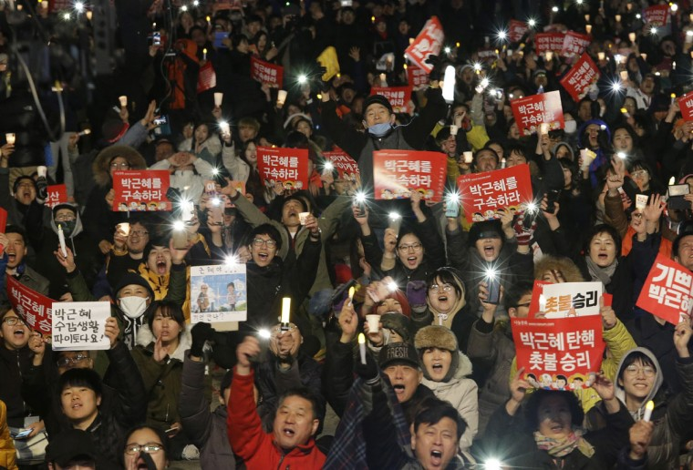 """Protesters shout slogans during a rally calling for impeached President Park Geun-hye's arrest in Seoul, South Korea, Friday, March 10, 2017. The Constitutional Court removed impeached President Park Geun-hye from office in a unanimous ruling Friday over a corruption scandal that has plunged the country into political turmoil and worsened an already-serious national divide. The signs read """"Park Geun-hye's arrest."""" (AP Photo/Ahn Young-joon)"""