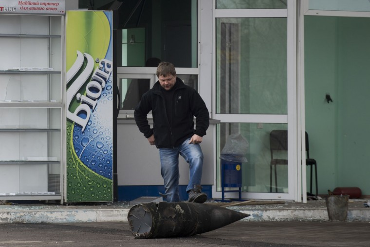 A man steps on a part of a missile in front of a small shop after a massive fire at a military depot in Balaklia, Ukraine, Friday, March 24, 2017. About 20,000 people were evacuated in Kharkiv region near the border with Russia when the fire broke out Thursday at one of Ukraine's largest military arsenals, which held huge stocks of large-caliber artillery rounds. (AP Photo/Evgeniy Maloletka)