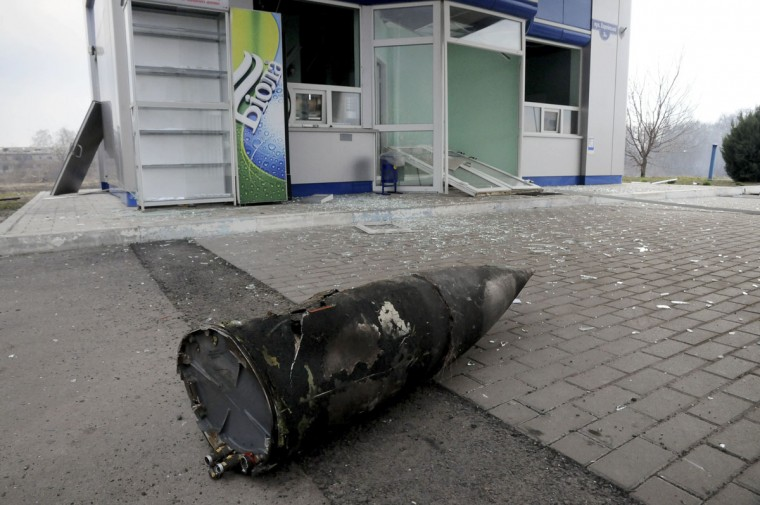 A part of a missile seen on the ground near a small shop as a fire rages at a military ammunition depot in Balaklia near Khrakiv in Ukraine on Thursday, March 23 2017. Around 20,000 people were evacuated Thursday in Ukraine's Kharkiv region near the border with Russia after a massive fire at a military arsenal. The fire at the depot in Balaklia, which holds large-caliber artillery rounds and is one of Ukraine's largest, erupted early Thursday, prompting the evacuation and Prime Minister Volodymyr Groysman to fly to the area to monitor the blaze, which is still raging. An area the size of 40 kilometers (25 miles) around the depot has been closed for flights. (AP Photo/Mykhailo Andriiv)