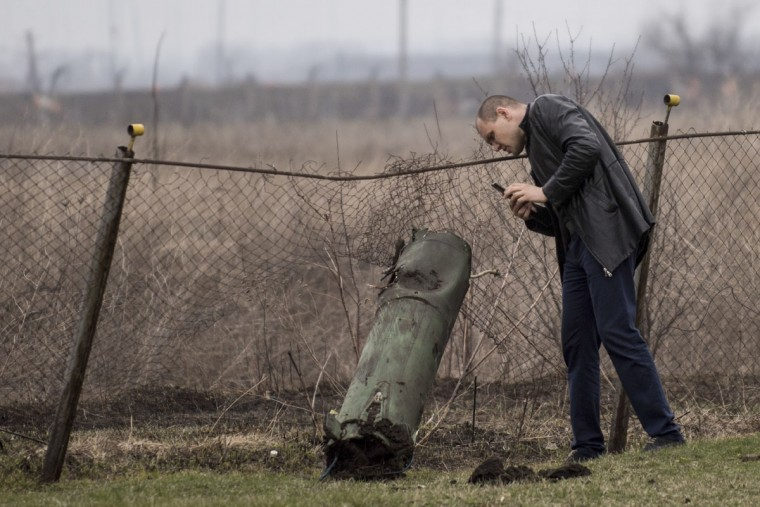 A man takes pictures of a part of a missile with his mobile phone after a massive fire at a military depot in Balaklia, Ukraine, Friday, March 24, 2017. About 20,000 people were evacuated in Kharkiv region near the border with Russia when the fire broke out Thursday at one of Ukraine's largest military arsenals, which held huge stocks of large-caliber artillery rounds. (AP Photo/Evgeniy Maloletka)