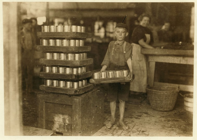 One of the small boys in J. S. Farrand P[ac]king Co. and a heavy load. J. W. Magruder, witness. Location: Baltimore, Maryland. 1909 July. (Lewis Hine/Photo courtesy LOC)