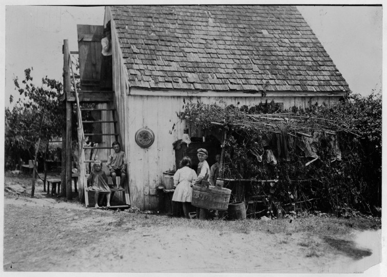 Name: Three families is the rule in these shacks, one room above and one below, but sometimes four families crowd in. Outdoor dining room at side[?] Maryland. 1909 July. (Lewis Hine/Photo courtesy of LOC)