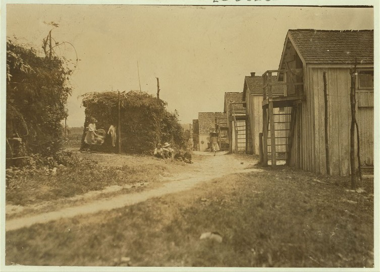 Shanties and cooking shacks on berry farm of Bottomley's, near Baltimore. Md. At times, four families live in one shanty: three families is the rule--two rooms. (See report July 10, 1909.) Location: Baltimore, Maryland. (Lewis Hine/Photo courtesy of LOC)