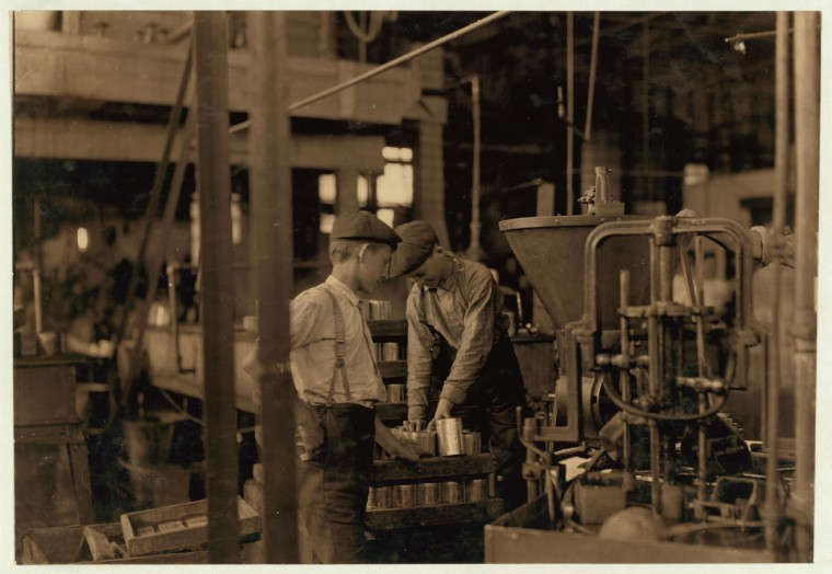 Title: A canning machine and some of the boy[s] Small boys work at and around these machines some of which[?][ are dangerous. J. S. Farrand Packing Co., Baltimore, Md. Witness--J. W. Magruder. July 7, 1909. Location: Baltimore, Maryland. (Lewis Hine/Photo courtesy of LOC)