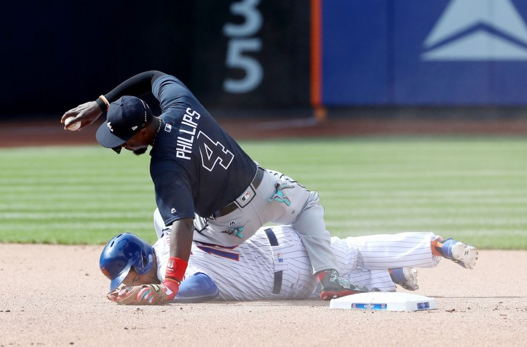 Brandon Phillips #4 of the Atlanta Braves makes the out as Travis d'Arnaud #18 of the New York Mets slides into second in the seventh inning during Opening Day on April 3, 2017 at Citi Field in the Flushing neighborhood of the Queens borough of New York City. (Photo by Elsa/Getty Images)