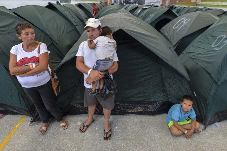 A family stands by tents in a shelter for people displaced by the floods in Mocoa, Putumayo department, southern Colombia on April 5, 2017. A state of economic emergency has been declared in the town of Mocoa in southern Colombia, after mudslides left more than 290 people dead. And local officials urged the government to dispatch more police and troops to secure the region and prevent the looting of abandoned homes. (LUIS ROBAYO/AFP/Getty Images)
