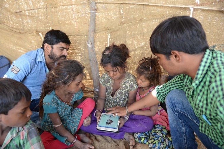 This picture taken on April 7, 2017 shows Anand Solanki (right), facilitator of the 'Zero Connect' programme, and teacher Deepsinh Vanola (top left), with a group of children of salt pan workers during a tent school workshop using an Internet-connected van, in the Little Rann of Kutch (LRK) region of Gujarat some 180km west of Ahmedabad. The children of Indian salt pan workers, drawn from the Agariya community in Gujarat state, accompany their parents in the remote and arid Little Rann of Kutch (LRK) region for nearly eight months of the year during the salt farming season. The 'Zero Connect' initiative provides basic education for the children in a joint initiative by the Agaria Heet Rakshak Manch, Digital Empowerment Foundation, Internet Society and Wireless for Communities groups. The initiative runs mobile workshops for the children, providing online access and education materials. (SAM PANTHAKY/AFP/Getty Images)