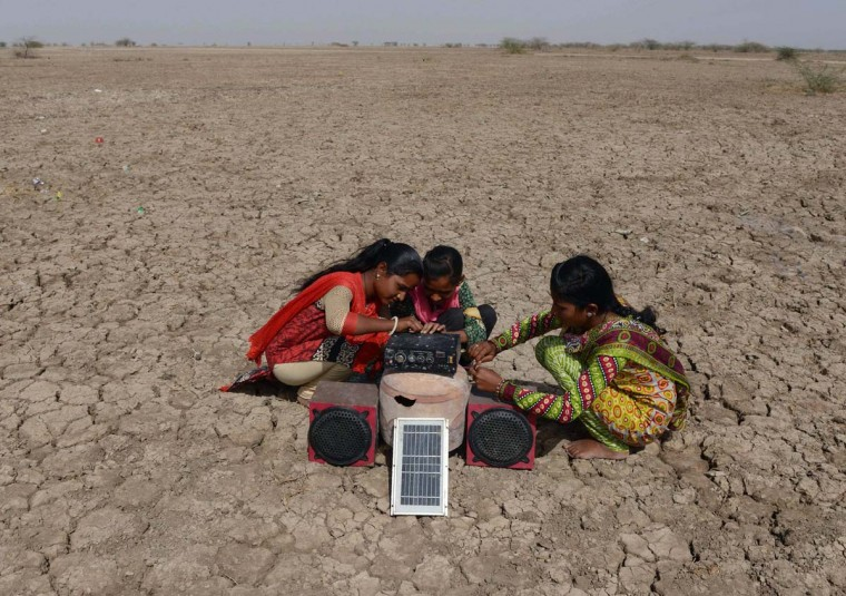 This picture taken on April 7, 2017 shows Indian salt pan worker Puja Ganeshbhai Muladiya (right) along with her sisters prepare for a traditional Garba (Gujarat's folk dance) as they connect a solar panel-powered music systems in the Little Rann of Kutch (LRK) region of Gujarat some 180km west of Ahmedabad. Indian salt pan workers of the Agariya community in Gujarat work in the remote and arid Little Rann of Kutch (LRK) region for nearly eight months of the year during the salt farming season. India is ranked third in gross amount of salt produced in the world, behind China and the United States, and the western state of Gujarat accounts for 77 percent of India's production. (SAM PANTHAKY/AFP/Getty Images)