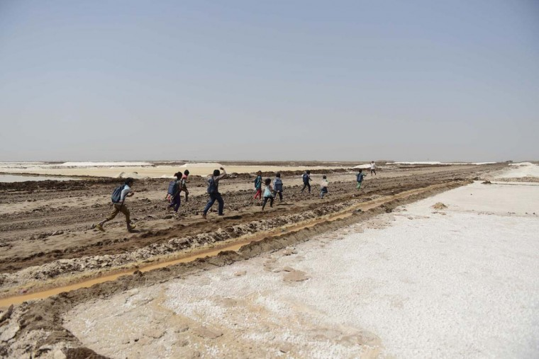 This picture taken on April 7, 2017 shows a group of children of salt pan workers leaving a tent school workshop with the 'Zero Connect' programme, in the Little Rann of Kutch (LRK) region of Gujarat some 180km west of Ahmedabad. The children of Indian salt pan workers, drawn from the Agariya community in Gujarat state, accompany their parents in the remote and arid Little Rann of Kutch (LRK) region for nearly eight months of the year during the salt farming season. The 'Zero Connect' initiative provides basic education for the children in a joint initiative by the Agaria Heet Rakshak Manch, Digital Empowerment Foundation, Internet Society and Wireless for Communities groups. The initiative runs mobile workshops for the children, providing online access and education materials. (SAM PANTHAKY/AFP/Getty Images)