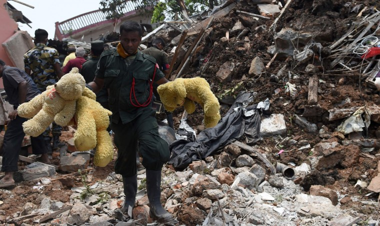 Sri Lankan army soldiers walk past damage houses after the collapse of a garbage dump in Meetotamulla, on the outskirts of Colombo on April 17, 2017. Sri Lanka has moved over 400 families to temporary shelters after tonnes of rotting garbage collapsed onto a slum on April 14, killing at least 28 people. (Ishara S. Kodikara/AFP/Getty Images)