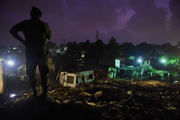A Sri Lankan military official stands overlooking damaged homes at the site of a collapsed garbage dump in Colombo on April 16, 2017. Hopes of finding anyone alive under a collapsed mountain of garbage in Sri Lanka's capital faded as the death toll reached 23 with another six reported missing, police said. Hundreds of soldiers, backed by heavy earth moving equipment were digging through the rubbish and the wreckage of some 145 homes that were destroyed when a side of the 300-foot (90-metre) high dump crashed on April 14. (Ishara S. Kodikara/AFP/Getty Images)