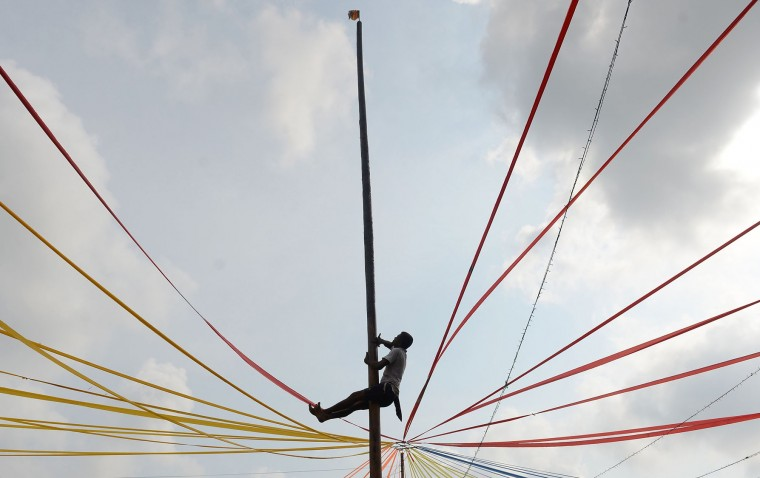 A Sri Lankan participant climbs a pole at Piliyandala near Colombo on April 14, 2017, as he takes part in the traditional festival game of 'grease tree' held to celebrate to mark the Sinhala and Tamil New Year. The new year which is common to both majority Sinhalese and minority Tamils dawned on April 14, but celebrations can go on for weeks. (Lakruwan Wanniarachchi/AFP/Getty Images)
