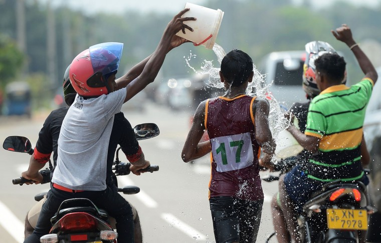 Sri Lankan spectators pour water onto a competitor during a road race held in Piliyandala near Colombo on April 14, 2017, as part of traditional festival games held to celebrate to mark the Sinhala and Tamil New Year. The new year which is common to both majority Sinhalese and minority Tamils dawned on April 14, but celebrations can go on for weeks. (Lakruwan Wanniarachchi/AFP/Getty Images)