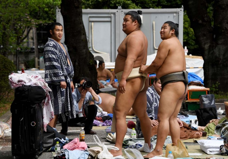 "Sumo wrestlers prepare ahead of a ""honozumo,"" a ceremonial sumo exhibition, on the grounds of Yasukuni Shrine in Tokyo on April 17, 2017. Sumo's top wrestlers took part in an annual one-day exhibition for thousands of spectators within the shrine's precincts. (TOSHIFUMI KITAMURA/AFP/Getty Images)"