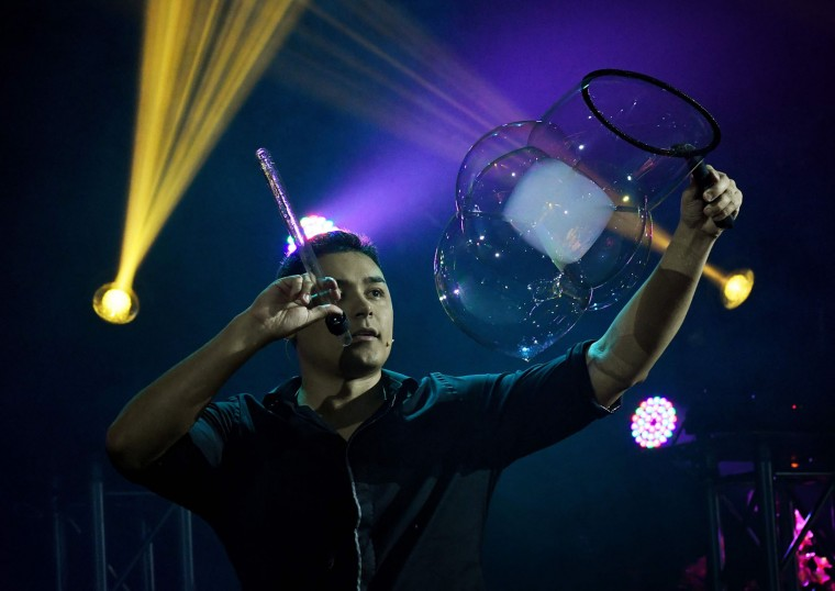 Bubble artist Deni Yang performs his act during his Mega Bubblefest Laser Show at the Discovery Cube Science Center in Santa Ana, California, on April 6, 2017. Deni, who is the son of famed bubble master Fan Yang, has followed in his father's footsteps and travels the world performing his bubble shows. His family holds the world record for largest soap bubble, measuring 167 feet long, that was created in Beijing, China in 2009. (Mark Ralston/AFP/Getty Images)