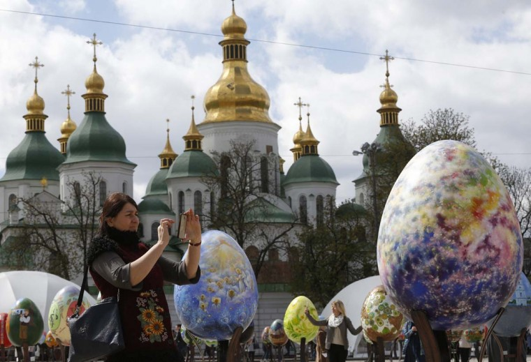 A woman takes pictures of Easter eggs on display in front of St. Sofia Cathedral in Kiev, Ukraine, Wednesday, April 12, 2017. (AP Photo/Sergei Chuzavkov)