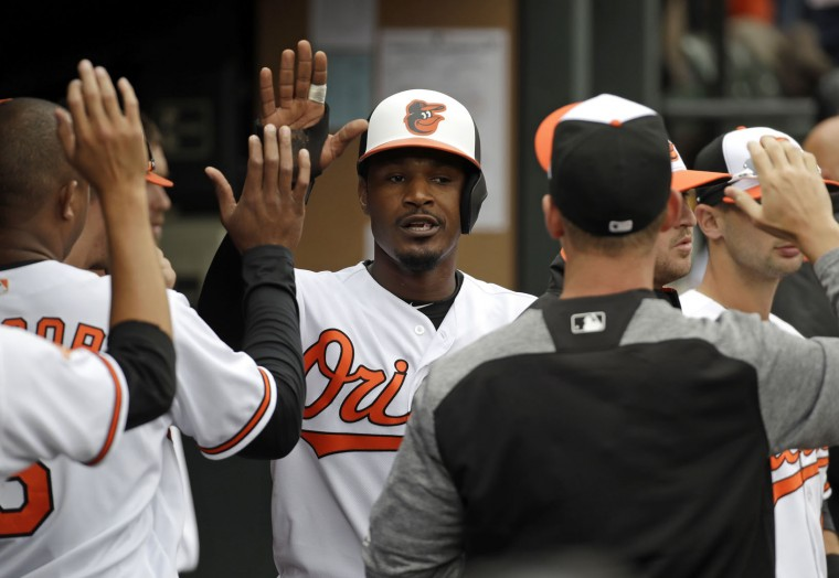 Baltimore Orioles' Adam Jones high-fives teammates in the dugout after scoring on a double by Mark Trumbo in the third inning of an opening day baseball game against the Toronto Blue Jays in Baltimore, Monday, April 3, 2017. (AP Photo/Patrick Semansky)