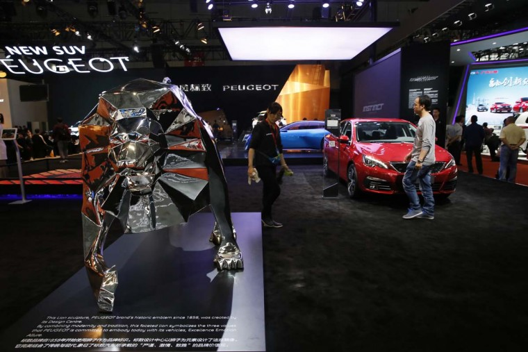 A worker walks past the Peugeot stand during the Auto Shanghai 2017 show at the National Exhibition and Convention Center in Shanghai, China, Wednesday, April 19, 2017. Models on display at Auto Shanghai 2017, the global industry's biggest marketing event of the year, reflect the conflict between Beijing's ambitions to promote environmentally friendly propulsion and Chinese consumers' love of hulking, fuel-hungry SUVs. (AP Photo/Ng Han Guan)