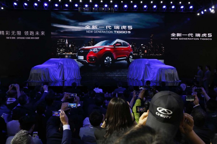 Visitors wait for the unveiling of the Tiggo 5 from Chinese automaker Chery during the Auto Shanghai 2017 show at the National Exhibition and Convention Center in Shanghai, China, Wednesday, April 19, 2017. Models on display at Auto Shanghai 2017, the global industry's biggest marketing event of the year, reflect the conflict between Beijing's ambitions to promote environmentally friendly propulsion and Chinese consumers' love of hulking, fuel-hungry SUVs. (AP Photo/Ng Han Guan)
