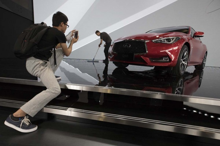 A visitor takes photo of the Lexus QX60 at the Auto Shanghai 2017 show at the National Exhibition and Convention Center in Shanghai, China, Wednesday, April 19, 2017. Models on display at Auto Shanghai 2017, the global industry's biggest marketing event of the year, reflect the conflict between Beijing's ambitions to promote environmentally friendly propulsion and Chinese consumers' love of hulking, fuel-hungry SUVs. (AP Photo/Ng Han Guan)