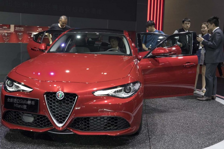 Visitors look at an imported car at the Alfa Romeo stand during the Auto Shanghai 2017 show at the National Exhibition and Convention Center in Shanghai, China, Wednesday, April 19, 2017. Models on display at Auto Shanghai 2017, the global industry's biggest marketing event of the year, reflect the conflict between Beijing's ambitions to promote environmentally friendly propulsion and Chinese consumers' love of hulking, fuel-hungry SUVs. (AP Photo/Ng Han Guan)