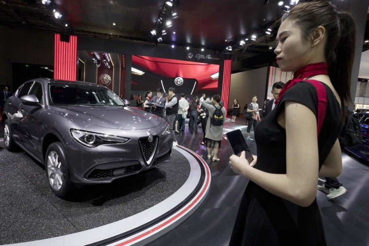 A worker waits for visitors to the Alfa Romeo stand during the Auto Shanghai 2017 show at the National Exhibition and Convention Center in Shanghai, China, Wednesday, April 19, 2017. Models on display at the Auto Shanghai 2017, the global industry's biggest marketing event of the year, reflect the conflict between Beijing's ambitions to promote environmentally friendly propulsion and Chinese consumers' love of hulking, fuel-hungry SUVs. (AP Photo/Ng Han Guan)